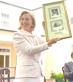 Showing the audience some memorabilia presented to her, Hillary Clinton at Montpelier during a ceremony honoring Dolley Madison. (WJCPL)
