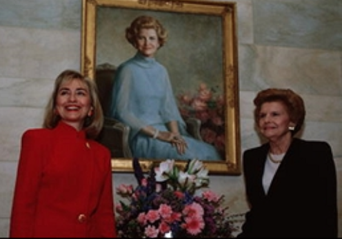 Hillary Clinton with Betty Ford, standing before the latter's White House portrait. (Getty)
